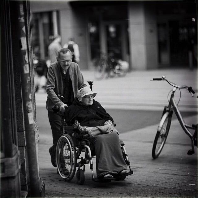 Personnes âgées dont une en chaise roulante.