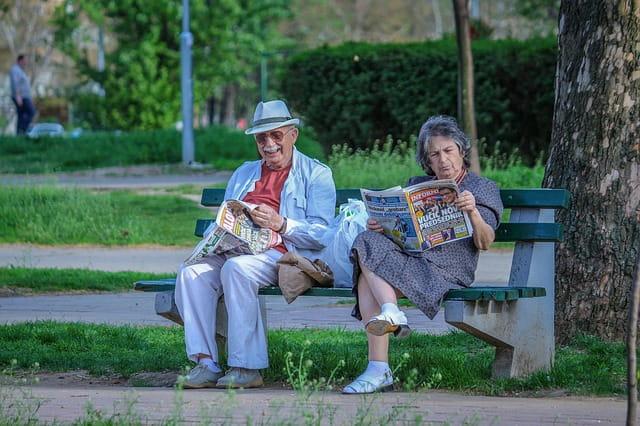 Deux personnes en maison de retraite sur un banc en train de lire le journal.