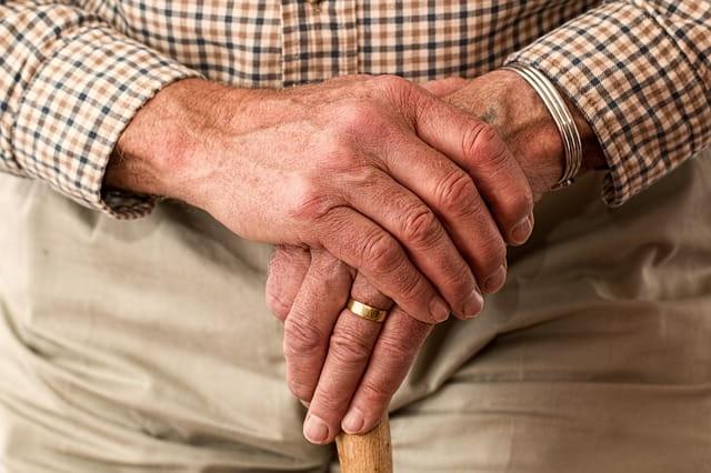 Mains d'une personne âgée sur une canne.