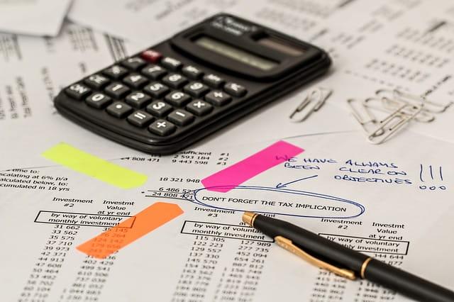 Calcul des impôts sur des papiers avec calculatrice, stylo et notes.