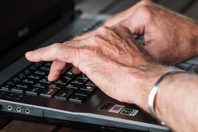 Les mains d'un senior qui tape un texte sur un ordinateur.