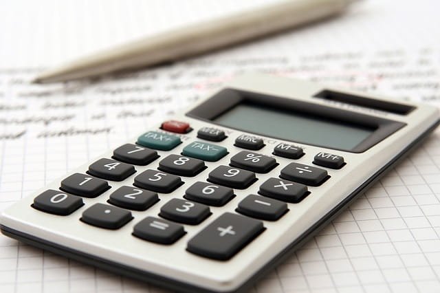 Une calculette, du papier et un crayon pour estimer les aides pour une personne âgée.