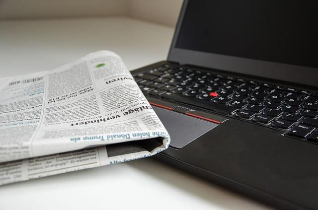 Un ordinateur et un journal papier.