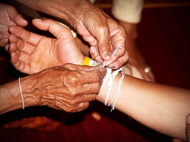 Mains d'une personne âgée accrochant un bracelet au poignet d'une jeune fille.