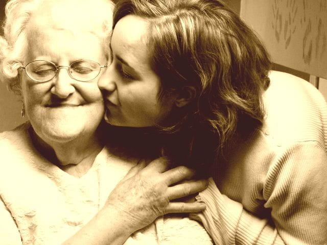 Jeune fille qui embrasse sur la joue une femme âgée en maison de retraite.