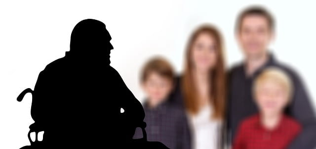 Silhouette d'un homme âgé dans un fauteuil roulant et famille en couleurs en arrière plan.