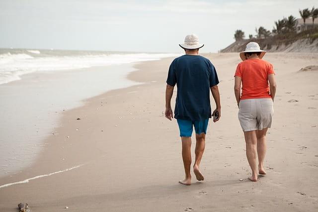 Photographie d'un couple de retraités marchant le long d'une plage.