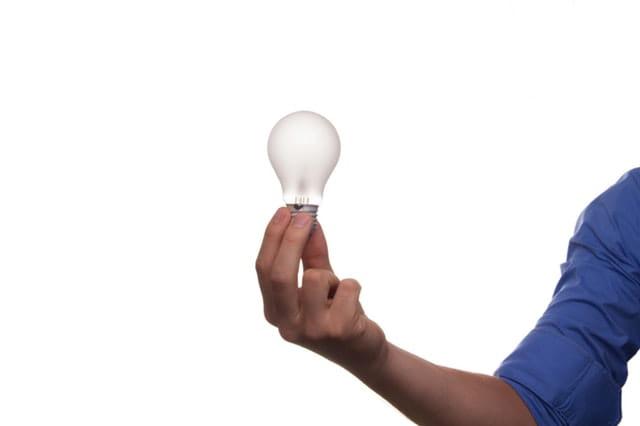 Main d'un homme tenant une ampoule.