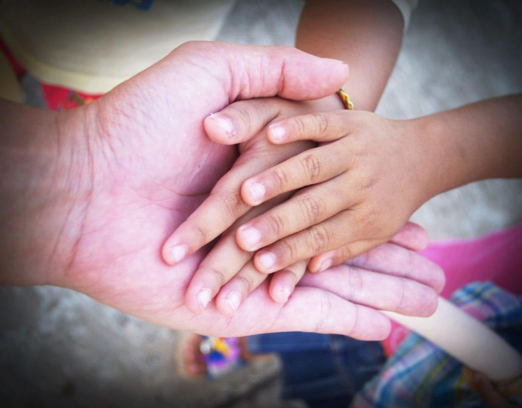 Personnes âgées tenant la main de ses petits-enfants.