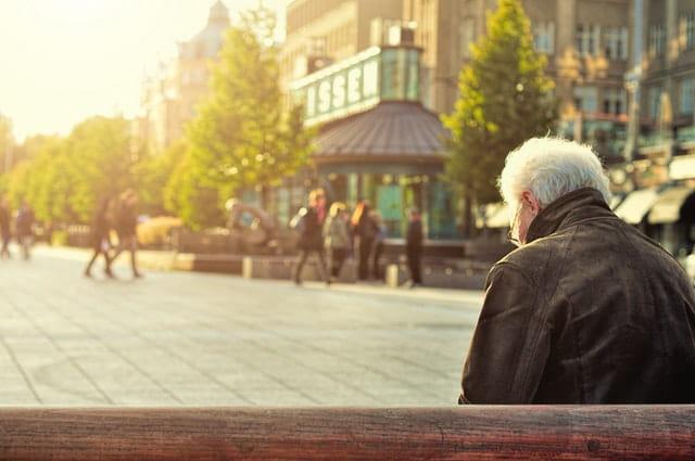 Photographie d'une personne âgée assise sur un banc.