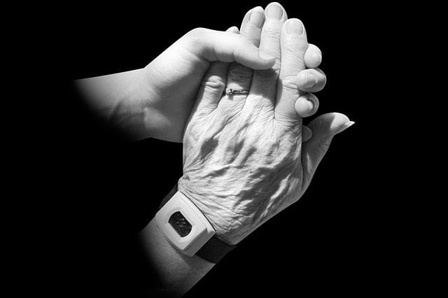 Main d'une personne âgée soutenue par la main d'un aidant.