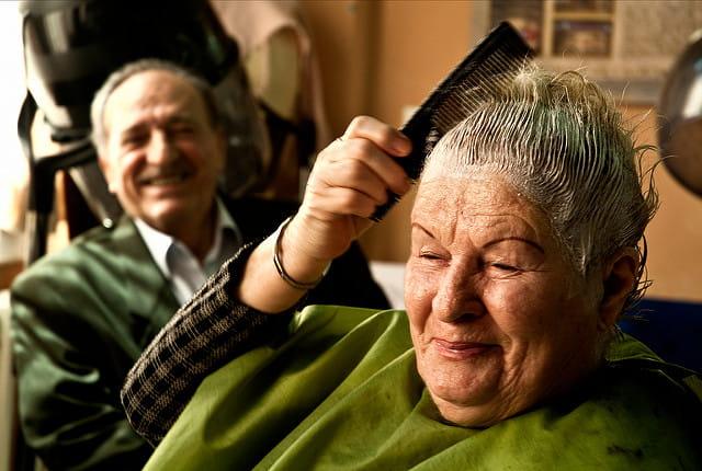 Une personne âgée en maison de retraite est en train de se faire une coloration tandis que son compagnon rie.
