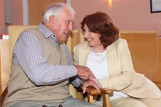 Un père âgé et sa fille discutant et riant dans une maison de retraite.