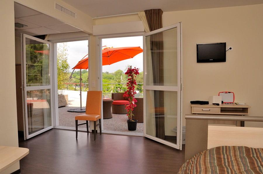 Une chambre de maison de retraite Senectis avec terrasse.