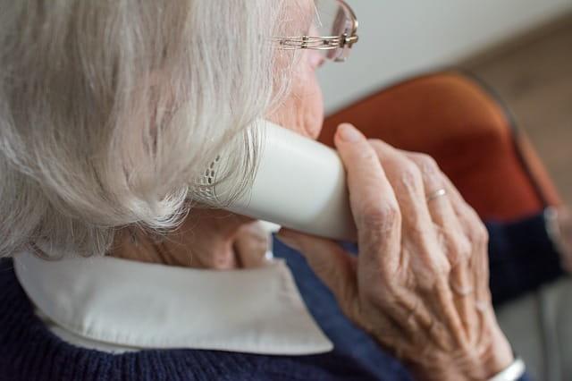 Personne âgée demandant des informations sur les aides sociales en maison de retraite.