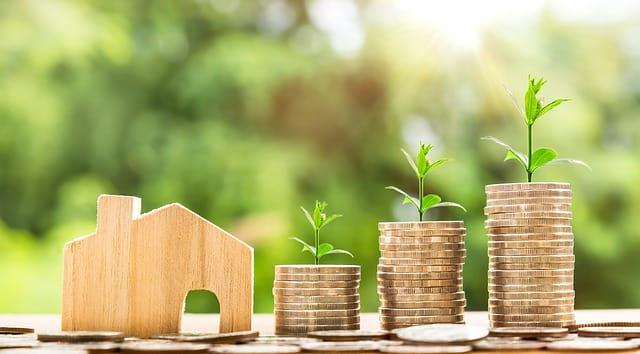 Petite maisonnette en bois à côté de pièces de monnaie évoquant les aides sociales au logement en EHPAD.