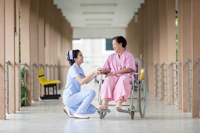 Résidente d'une maison de retraite en fauteuil roulant accompagnée d'une aide-soignante.