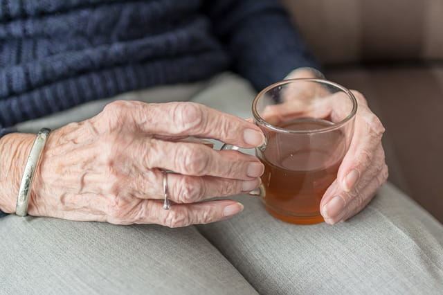 Mains de femme âgée tenant une tasse de thé.