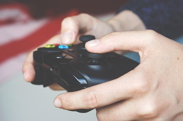 Mains d'une personne tenant une manette de jeux vidéo.