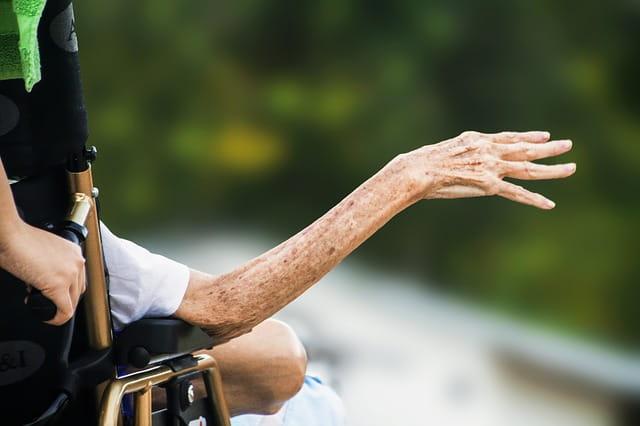 Une personne âgée dans un fauteuil qui tend une main.
