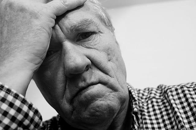 Homme âgé triste se tenant la tête.