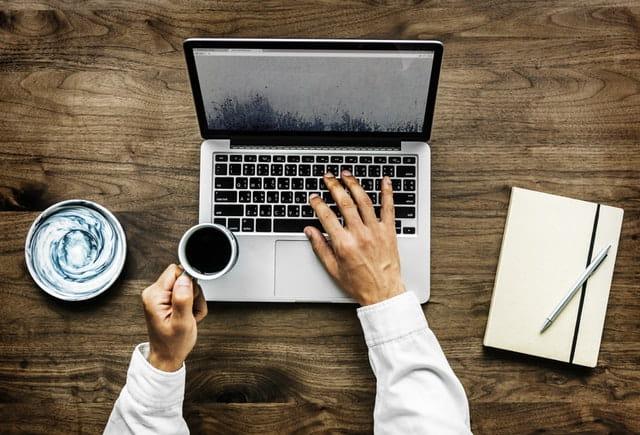 Une personne un tasse à la main devant son ordinateur.