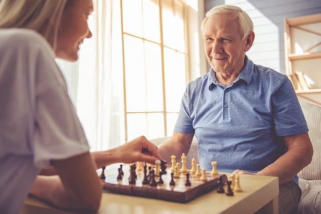 Femme qui joue aux échecs avec un homme âgé en maison de retraite.