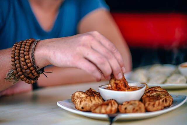 Main d'une personne qui tient de la nourriture et la trempe dans la sauce.