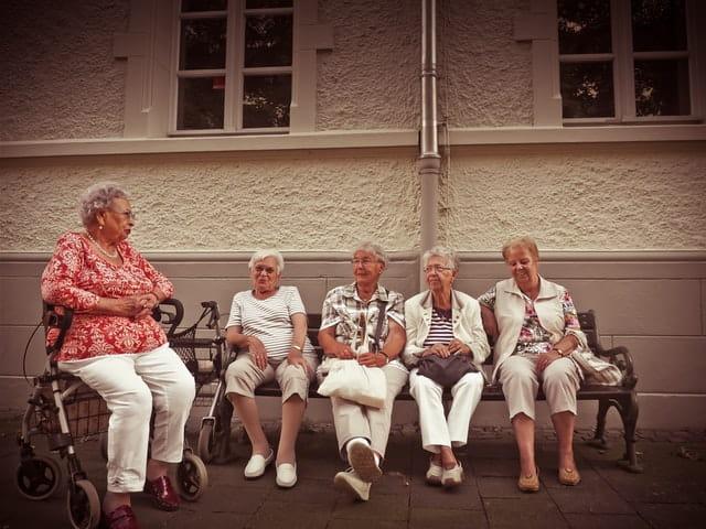 Personnes âgées assises sur un banc en train de discuter.