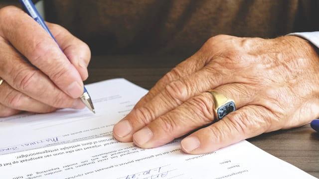 Personne âgée en train de signer son contrat d'hébergement temporaire en EHPAD.