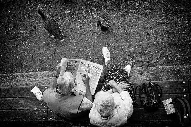Deux retraités sur un banc qui lisent le journal à propos de la revalorisation du point de retraite complémentaire.