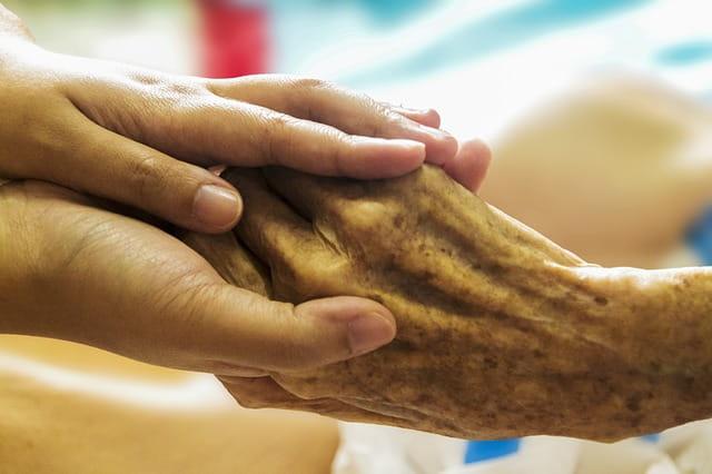 Main d'une aide-soignante tenant la main d'une personne âgée en maison de retraite.