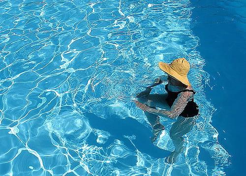 Une personne âgée dans une piscine en train de faire une séance de balnéothérapie en maison de retraite.