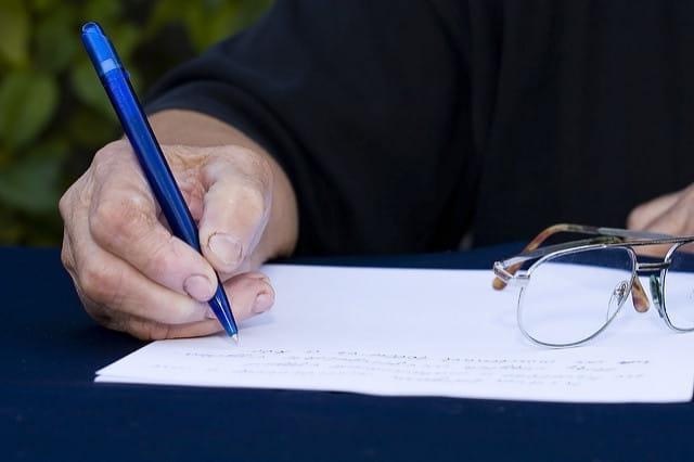 Une personne âgée remplissant un formulaire.