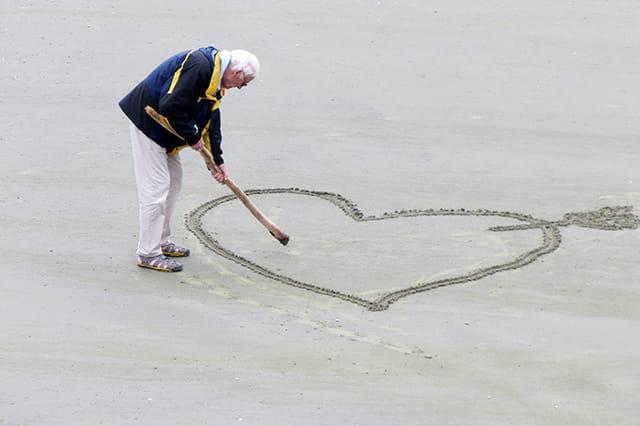 Personne âgée en train de dessiner un cœur dans le sable pour Noël.