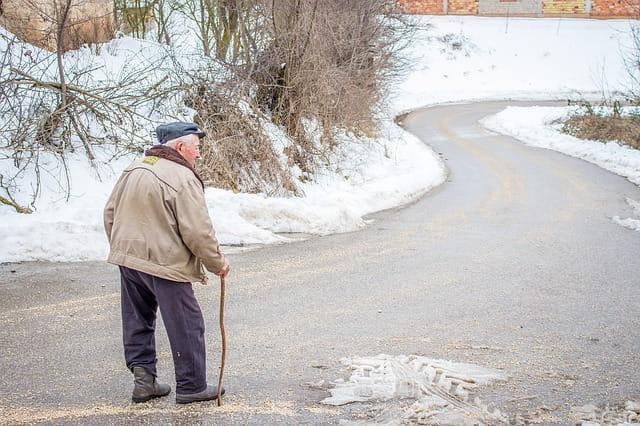 Un monseiur âgé s epromène sur une route enneigée.