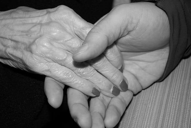 Deux mains qui se serrent, l'une appartenant à une personne âgée en maison de retraite..