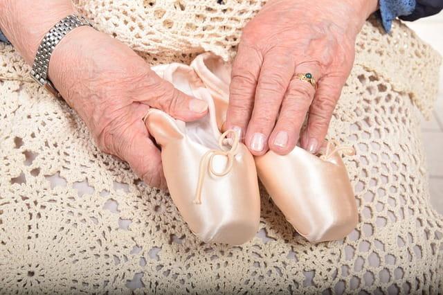 Une senior tenant des chaussons de danse.