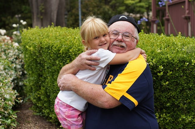Grand-père et petite-fille faisant un câlin dans le jardin d'une maison de retraite..