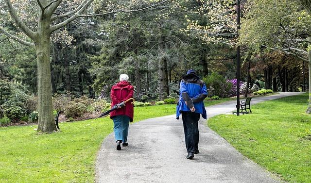 Deux personnes âgées se promènent en discutant.
