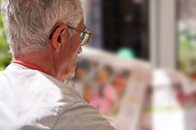 Homme retraité lisant un journal.