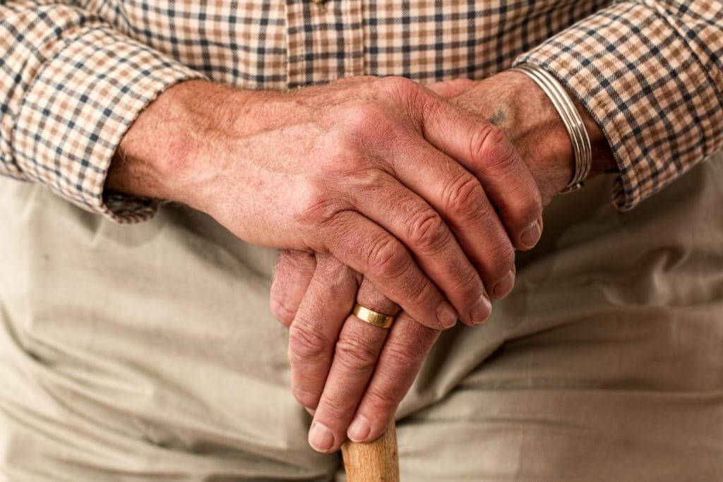 Ce sont des mains d'une personne âgées sur une canne.
