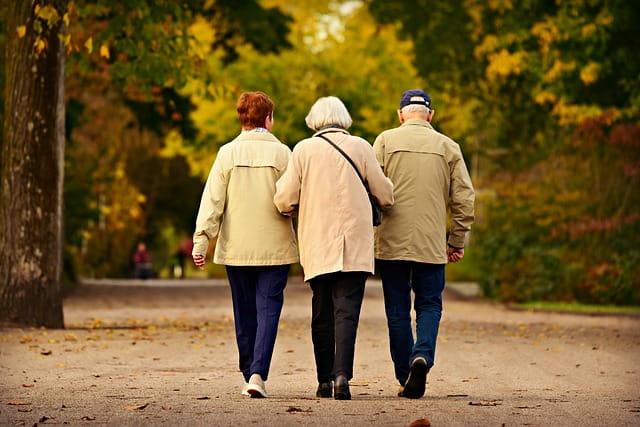 Personnes âgées en maison de retraite marchant ensemble.