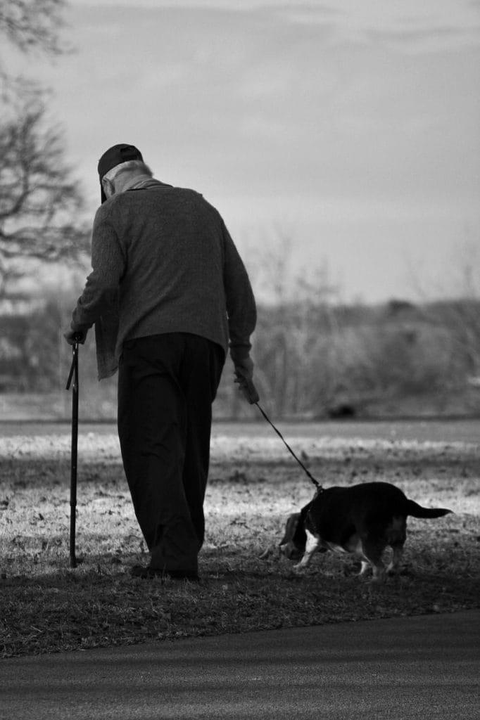 Une personnes âgées qui promène son chien.