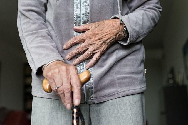 Une personne âgées qui tient une canne.