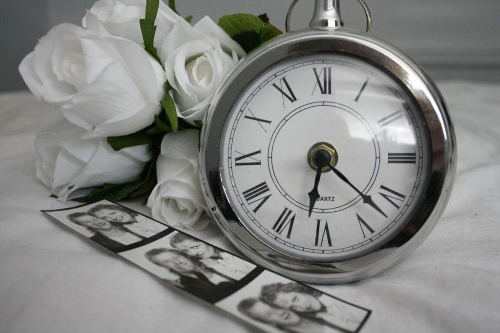 Photo en noir et blanc avec une horloge, des roses et des photos.