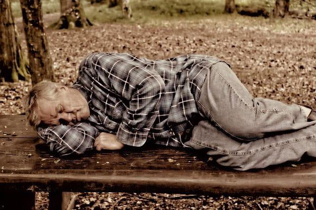 Une personne âgées allongée sur un banc.