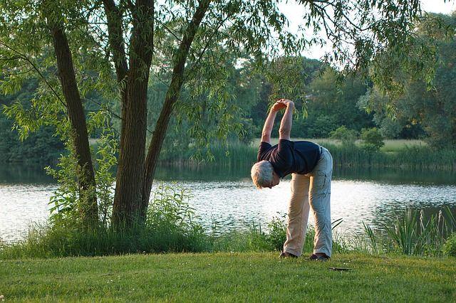 Un senior qui fait des étirements ( type yoga ).