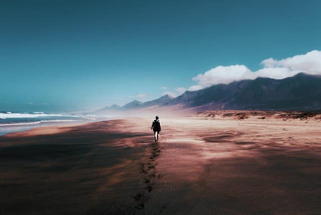Personne âgée qui marche seule sur une plage.