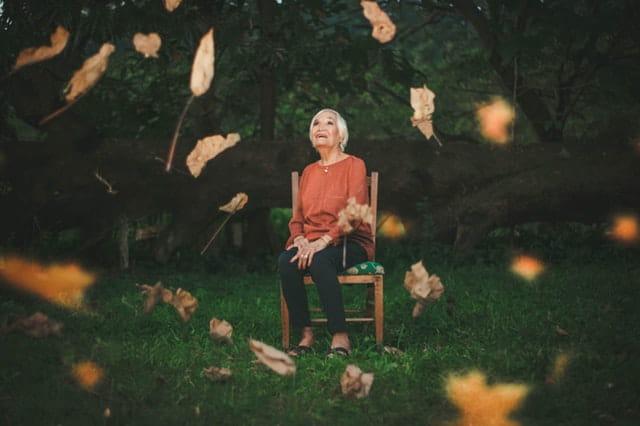 Une femme âgée assise au milieu de feuilles d'arbre.